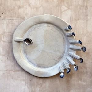 """מגדלנה חפץ, מתוך הסדרה אכלנו אותה, 2014-2005, תבליטי צלחות וסכו""""ם, קוטר ממוצע של כל צלחת 45 ס""""מ (צלם: שלמה סרי)"""