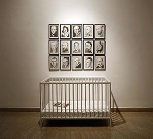 Raised by Man, אורי רדובן, 15 רישומי עפרון על נייר 23x31 ס״מ (כ״א), מיטת תינוק, 123x65x79 ס״מ, ספר (2019). צילום שלמה סרי
